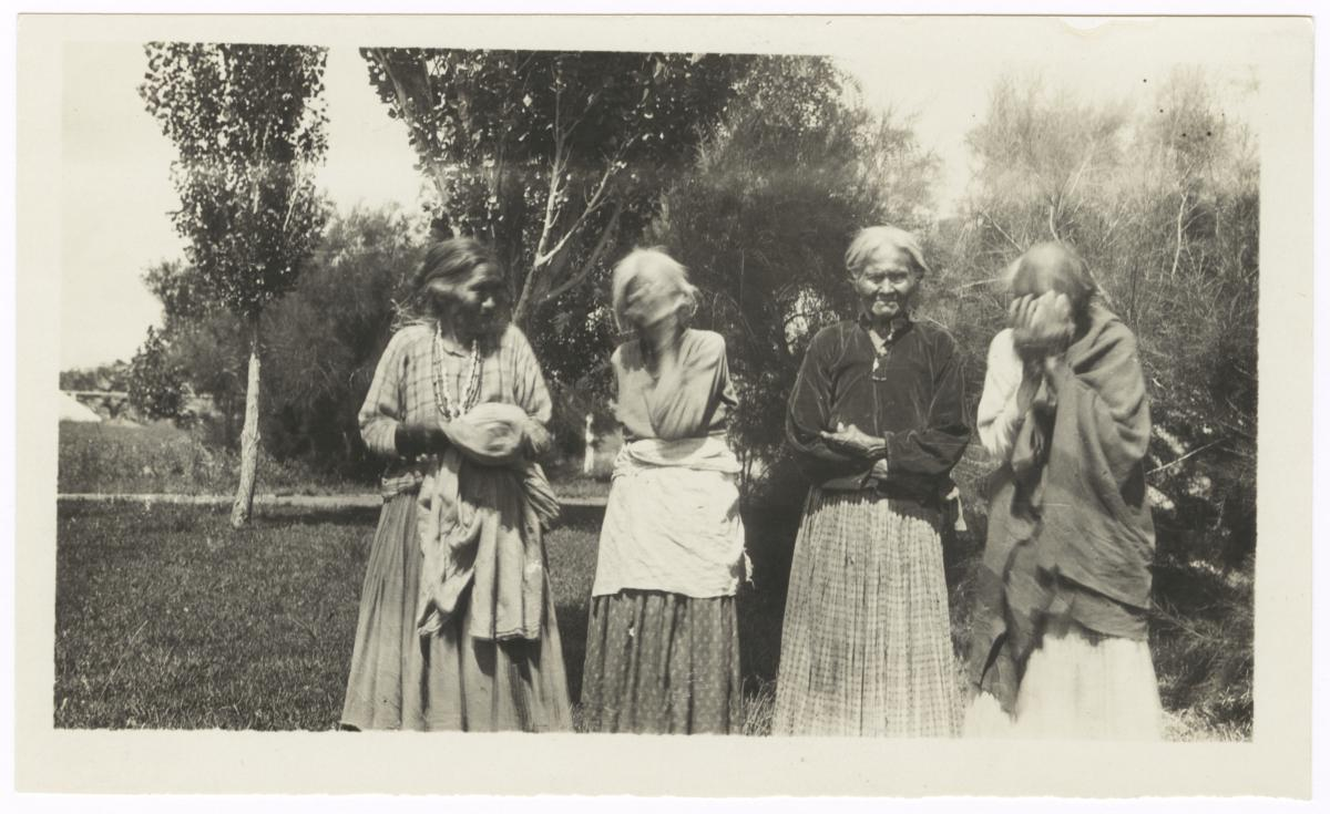 Four Elderly  Women Standing Outside, Two Covering Their Faces from the Camera