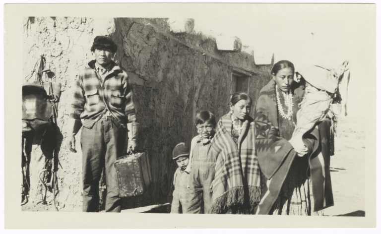 Man, Woman and Four Children in front of a Building
