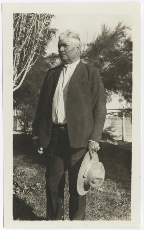 Older Native American Man in Suit, with a Hat in His Hands