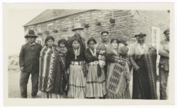 Group of Men, Women and Children Standing in Front of a Building