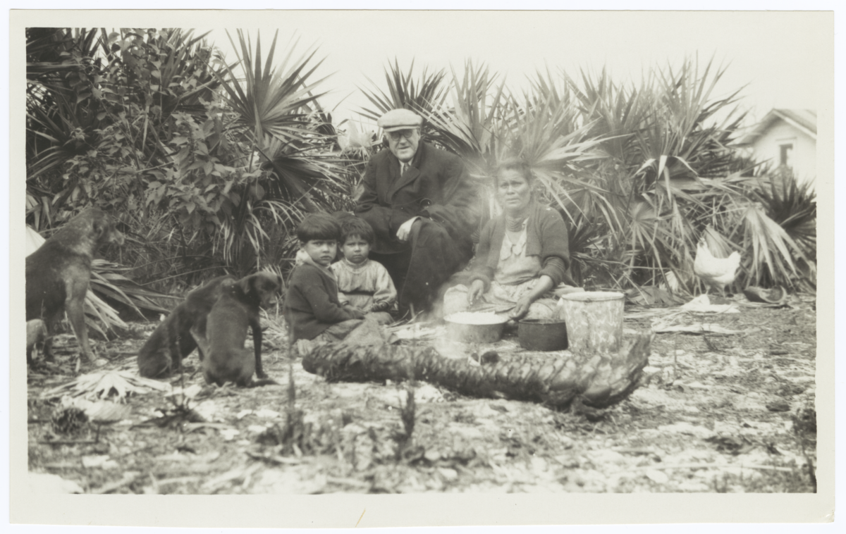 American Indian Woman Cooking While Children and a Visiting Man Sit nearby, Florida