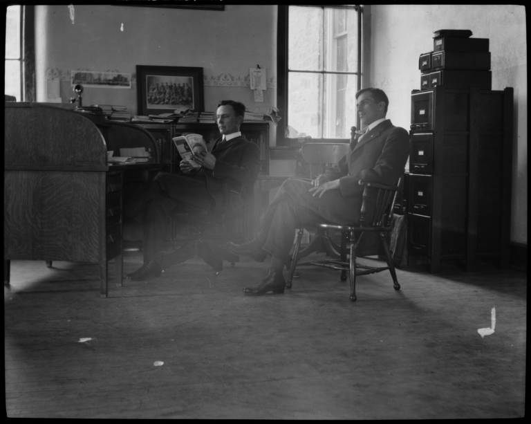 Two Men Sitting in a Office, Reading