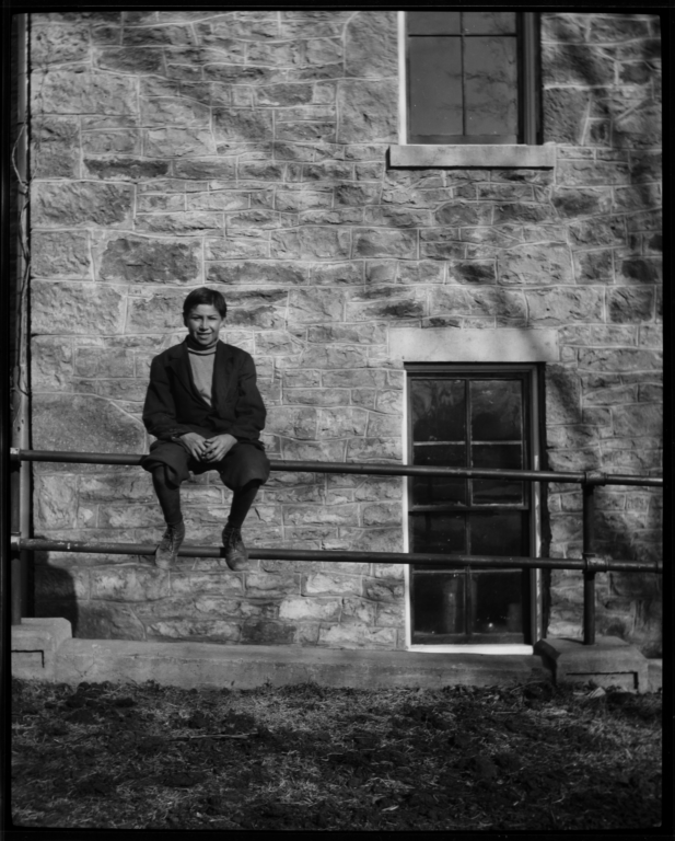 Young Man Sitting on a Fence in front of a Stone Building, Haskell Institute, Lawrence, Kansas