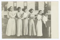 Six Young Women Standing in Size Order Outside; a Stone Building Is Backdrop