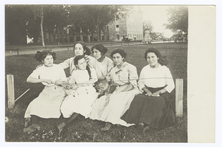 Six Young Women Sitting on a Low Bench on the Lawn