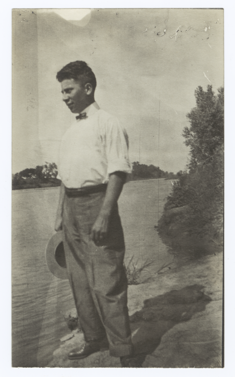 Young Man Holding a Hat Standing by a Lake