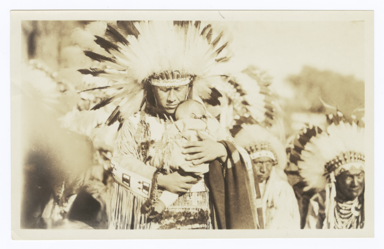 Men in Full Native American Regalia, front Man Holds an Infant Tenderly