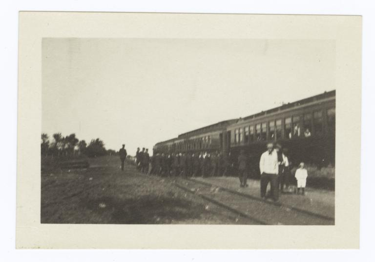 Group of Uniformed Students Entering a Train Car; from a Distance
