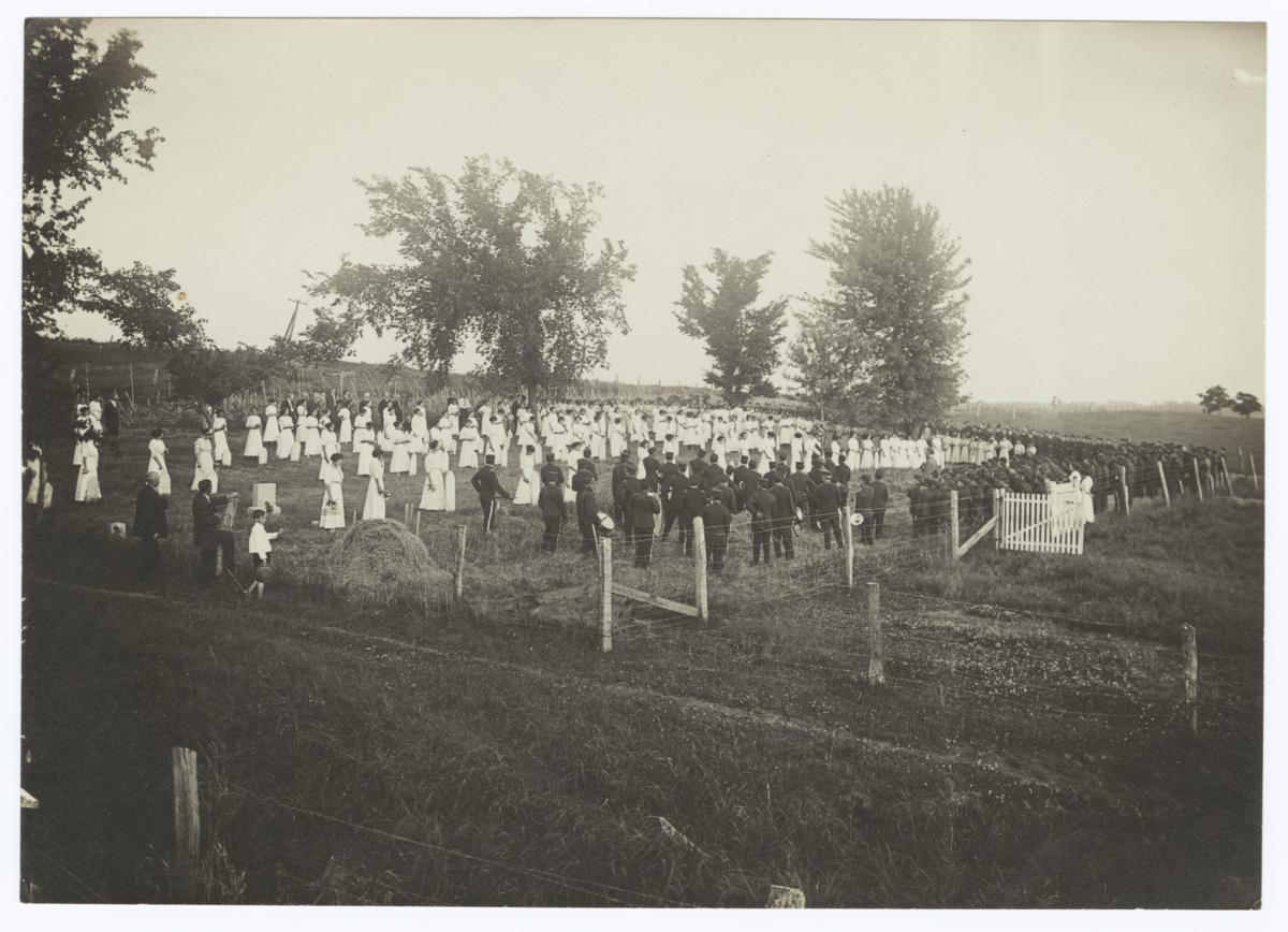 Large Group of People on a Field, Marching Band in Uniform on one Side and  Women in White Dresses