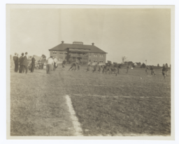 Football Game in Progress with Spectators Standing around the Field's Edge, Haskell Institute