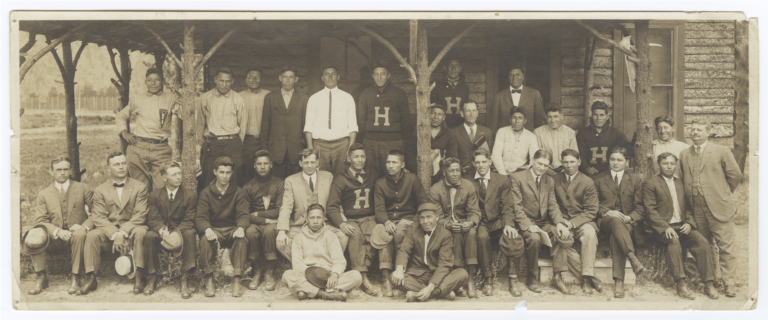 "Men in Suits or ""H"" Sweaters in front of a Log Cabin at the First National YMCA Training Camp"