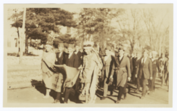 Haskell Institute Members Marching in a Parade, in Native American Dress, Holding School Banner