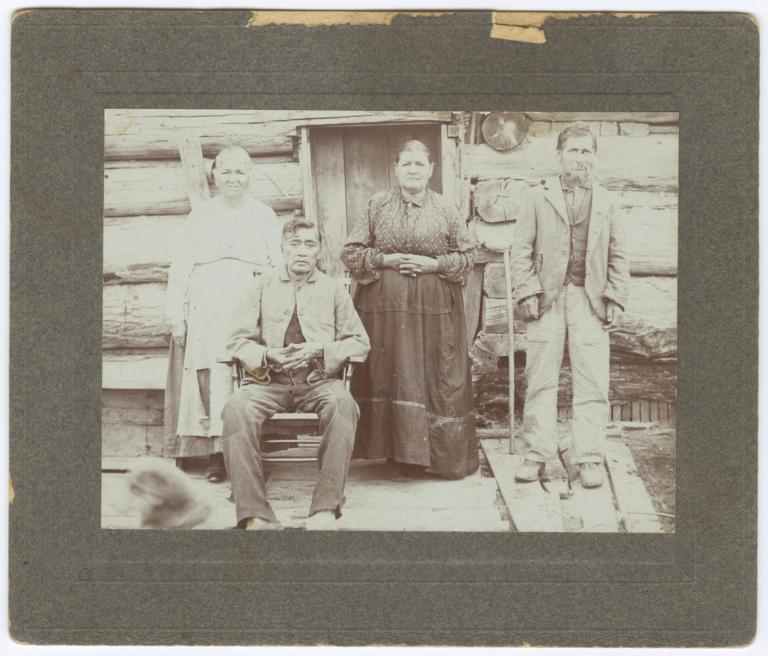 Four Older Ojibwa Indians in front of a Log Home