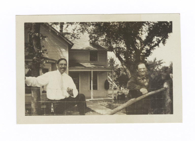 Two Men behind Fence, in front of House