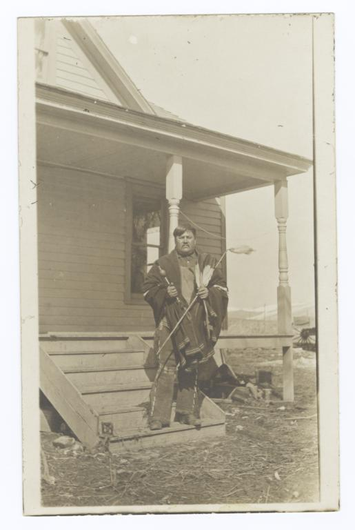 American Indian Man Posing in Front of a House