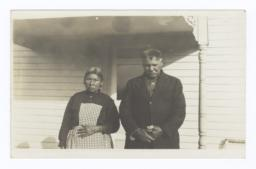 Elder American Indian Couple in front of House
