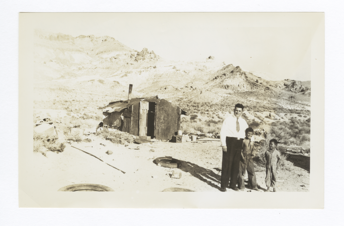 Reverend Floyd O. Burnett and Two American Indian Boys in front of Shack, Beatty, Nevada