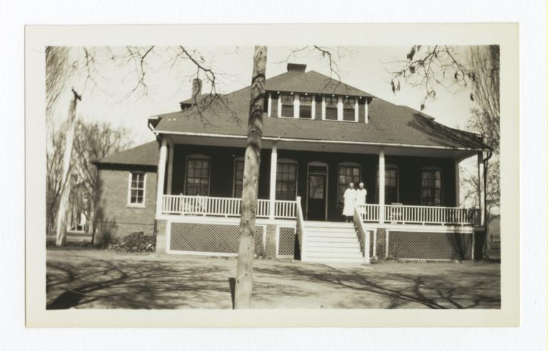 Front View of What Appears to Be a Home with Two Women Standing on the Porch