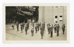 Brass Band in Uniform and Formation to Perform, Gathered in front of a Brick Building