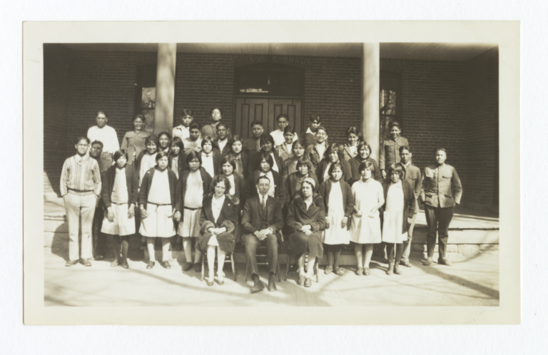 Large Group of Unidentified People in front of a Building, Three Adults Seated in Front Row