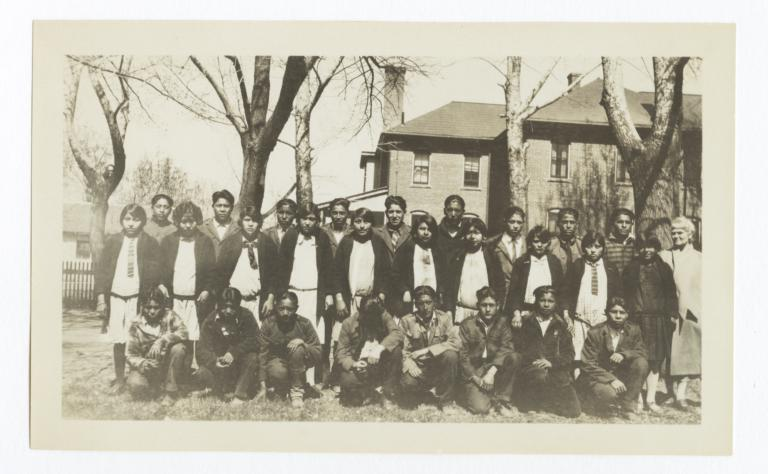Large Group of Unidentified Young People in in Yard near Buildings