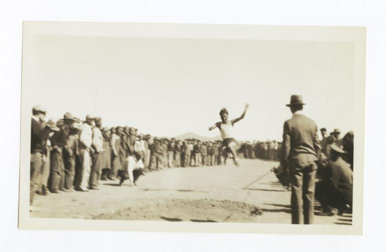 At a Track and Field Sporting Event, a Man in the Midst of a Long Jump