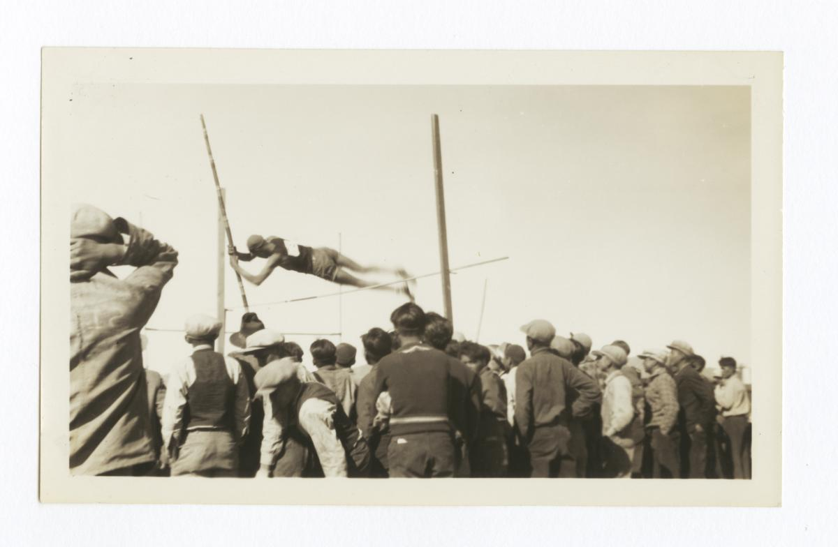 At a Track and Field Sporting Event, a Man in the Midst of the High Jump Surrounded by Crowd