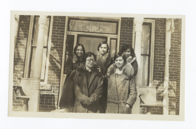 Five Women in Coats Posing on the Porch