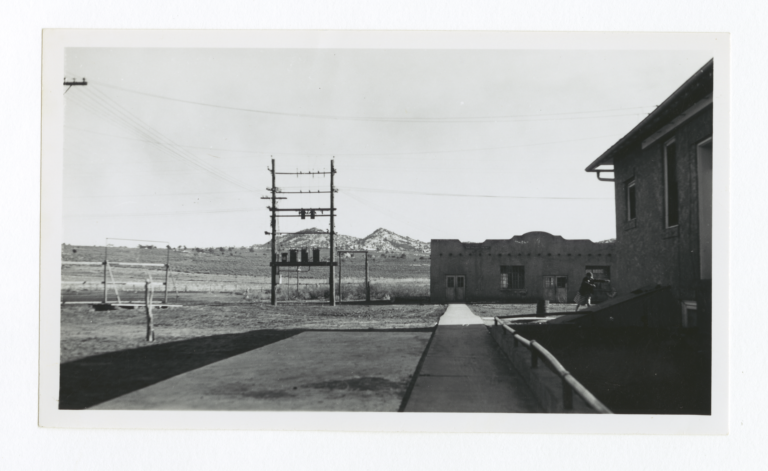 Unidentified Buildings, Electrical Wires Grid and Mountains in the Background