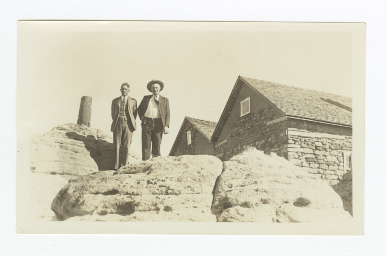 G.E.E. Lindquist and Another Man in a Hat on Rock Outcroppings near Stone Building