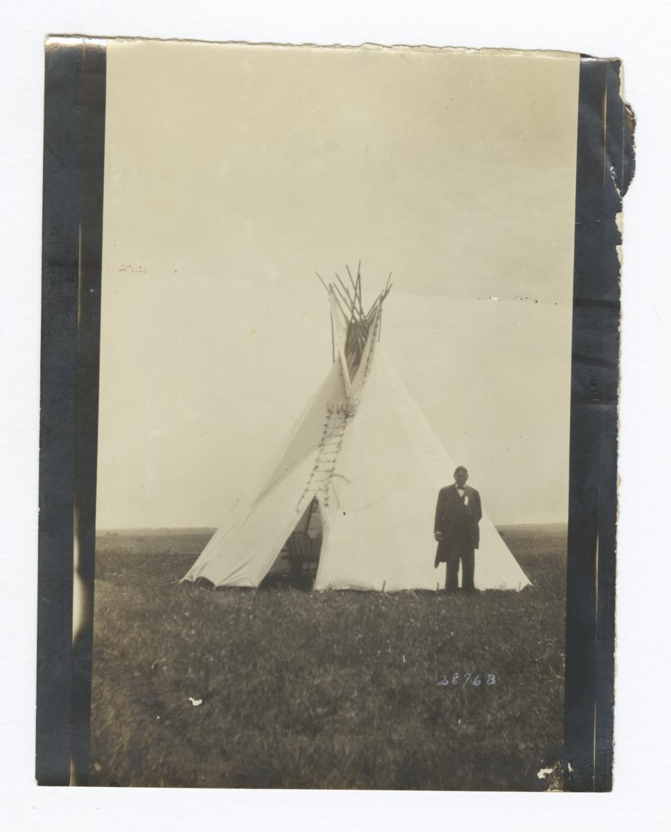 Man in Formal Attire Standing next to a Tipi