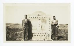Two Men Standing next to a Monument in a Field