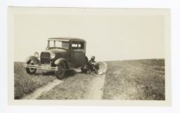 Man Sitting on Rutted Road next to Automobile