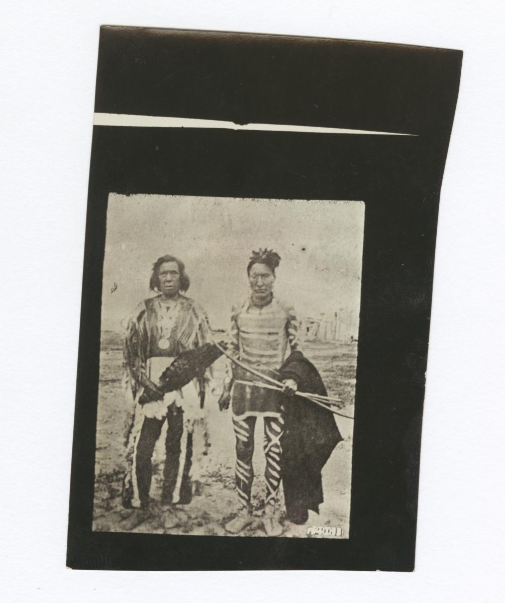 Two Native American Men Wearning Ceremonial Dress, One with Body Paint, Carrying Bow and Arrows
