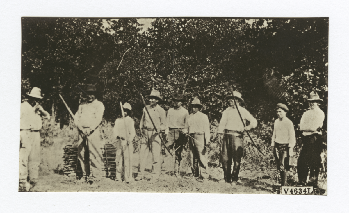 Group of Men Lined up with Bows and Arrows, Man on Left of Frame Points toward a Target
