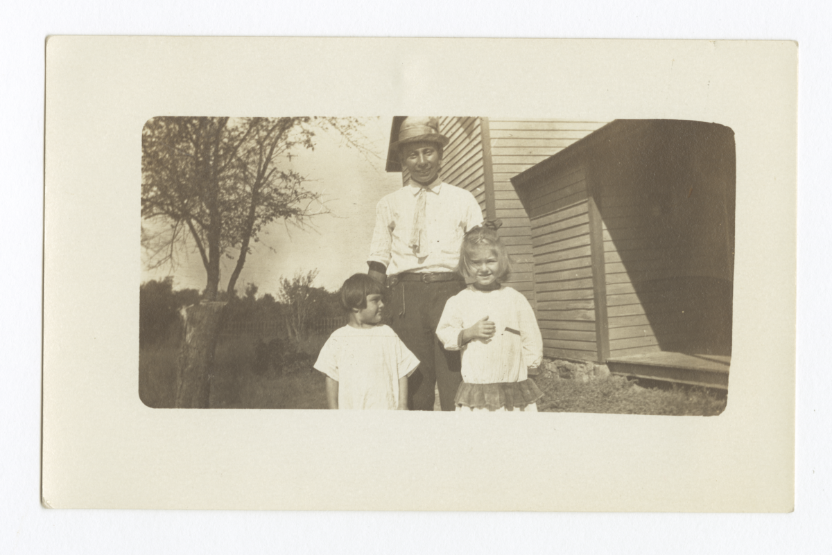 Man and Two Children Outdoors in front of a House