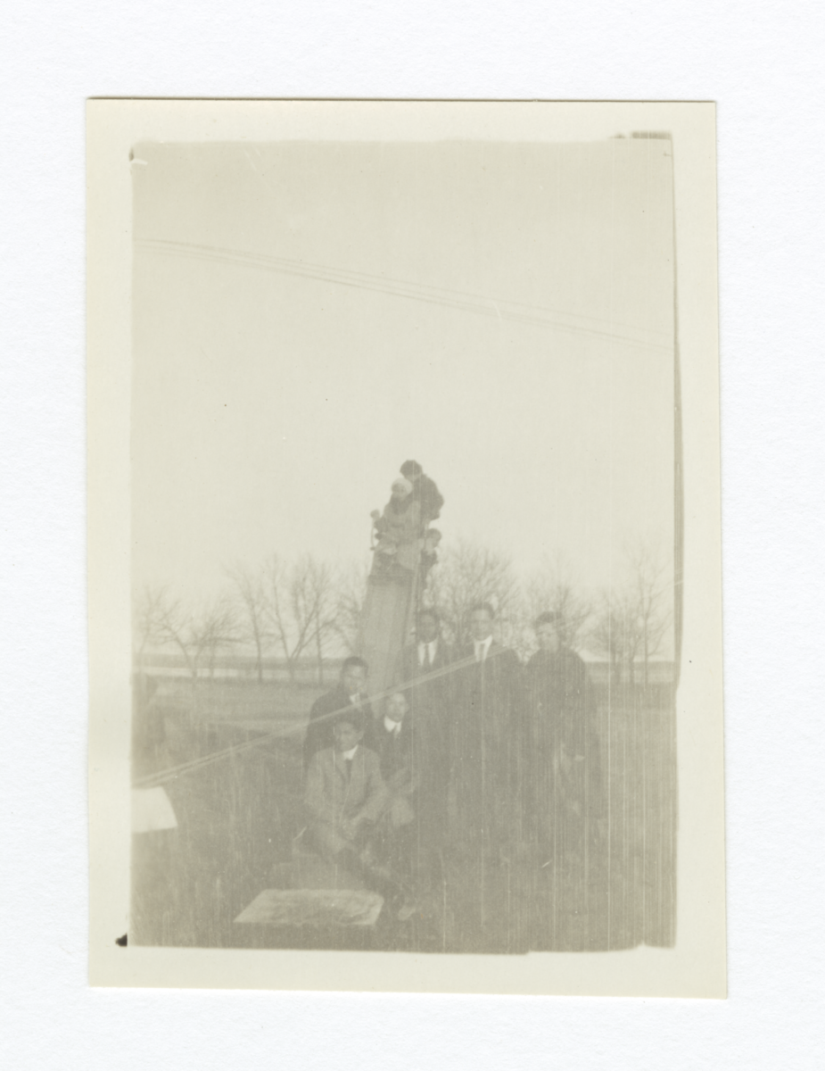 Group of Men and Children Outside Gathered around or on a Slide