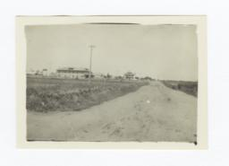 Landscape View down a Dirt Road with Buildings in the Distance