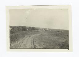 Landscape View down a Dirt Road with Buildings in the Far Distance