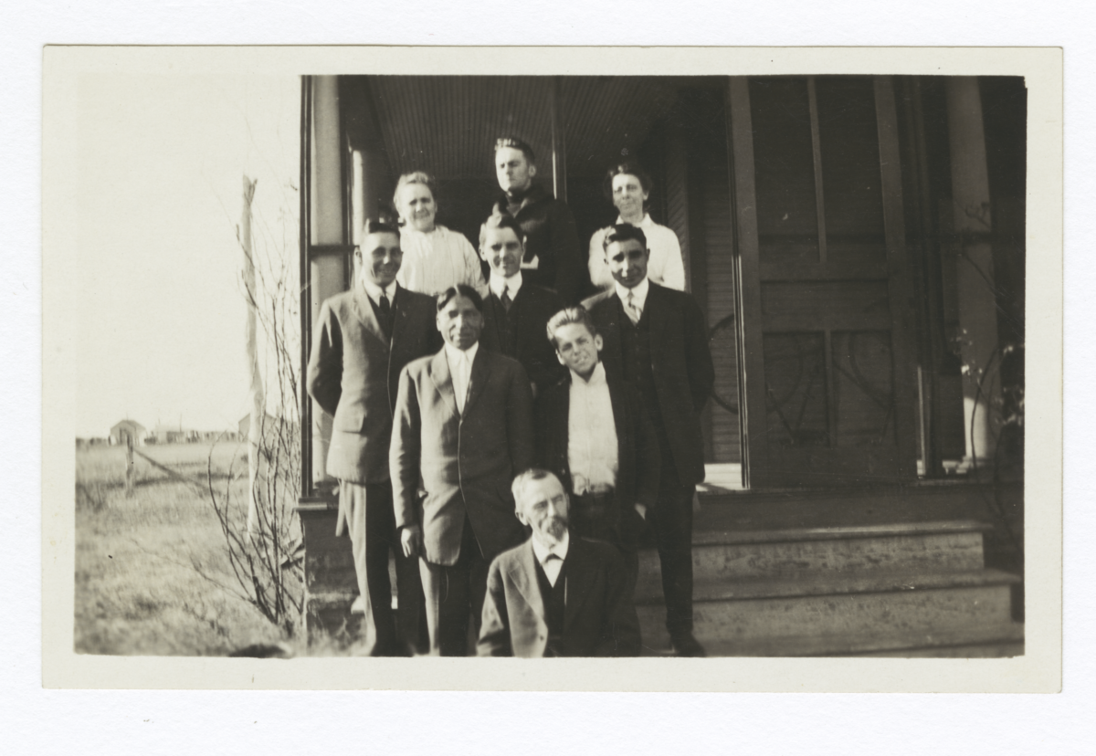 Group of People Standing on the Steps Leading to a Porch