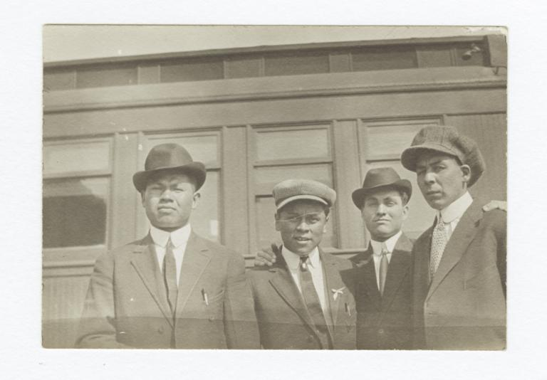Four Men Wearing Suits and Ties Posing in front of a Building