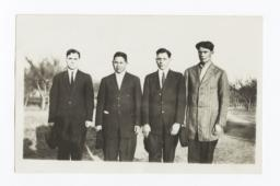 Four Men Standing in a Field Wearing Suits and Ties