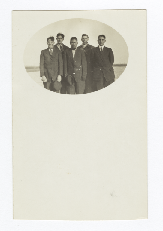 Five Men Standing in a Field Wearing Suits and Ties