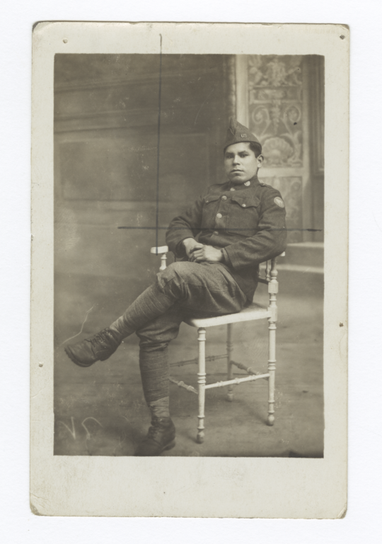 Man Wearing a Uniform and Sitting with Legs Crossed in a Chair