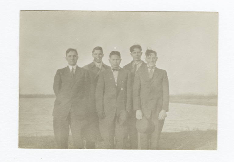 Five Men Wearing Suits and Ties Posed Standing Next to a Small Pond or Lake
