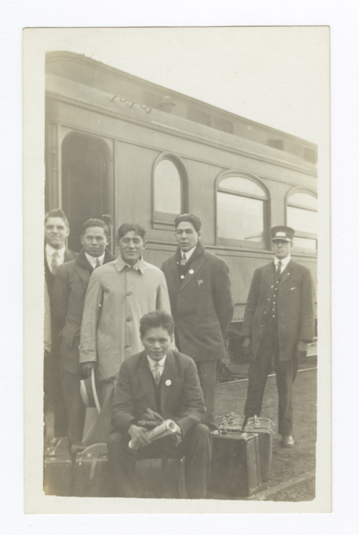 Five Men with Luggage Standing next to a Train and Conductor