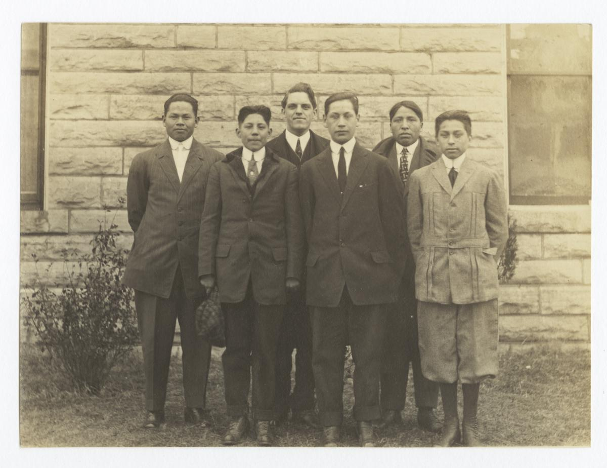 Neatly Attired Group of Men Standing in front of a Stone and Mortar Building