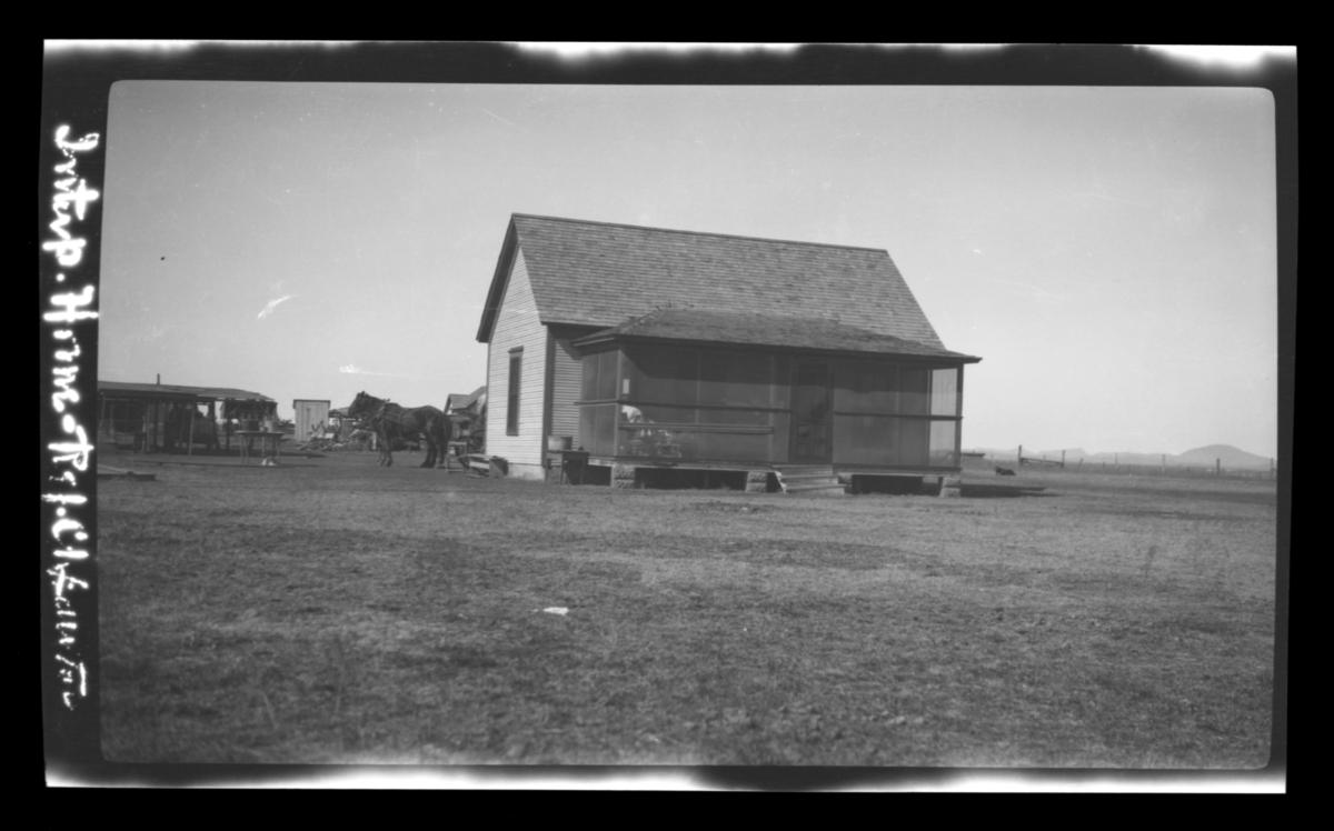 Small Home with an Enclosed Porch, Horse and Buggy in Back
