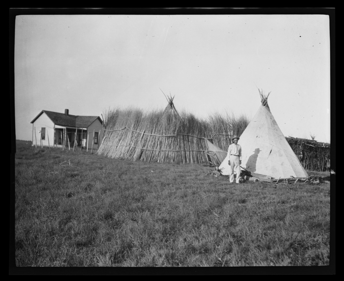 Man in a Yard with Two Tipis, a Thatched Fence, and Small House