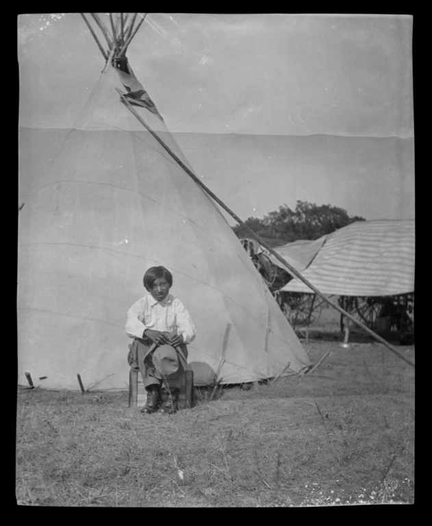 American Indian Boy With a Hat Sitting in front of a Tipi